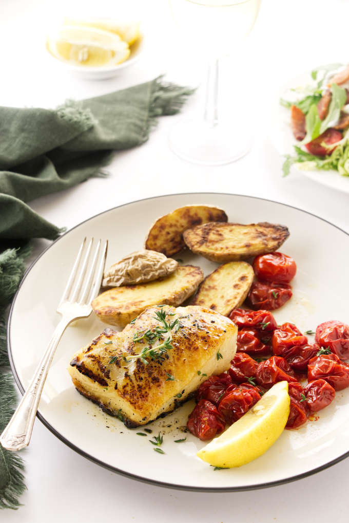 Plated Chilean Sea Bass with roasted veggies and lemon wedge