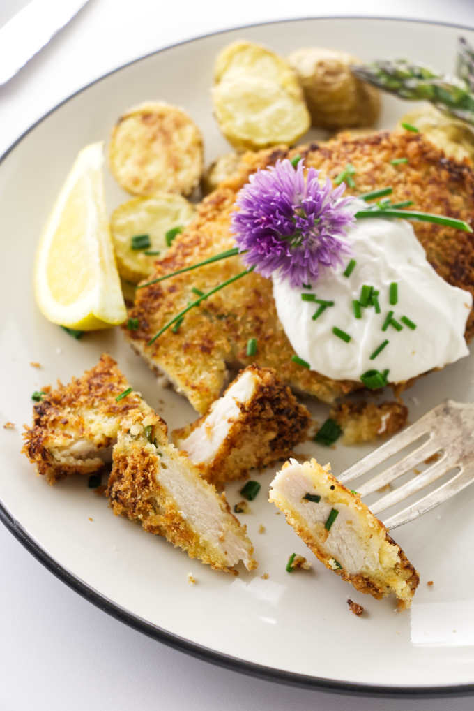 A serving of crispy chicken with sour cream and chives and a bite on a fork