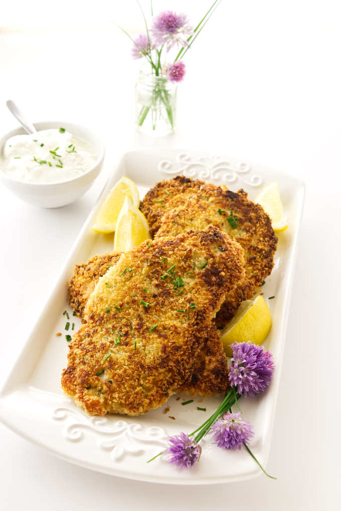 Platter of Pan Fried Chicken Breast cutlets with lemon wedges and chive blossoms. Dish of sour cream and flowers in background