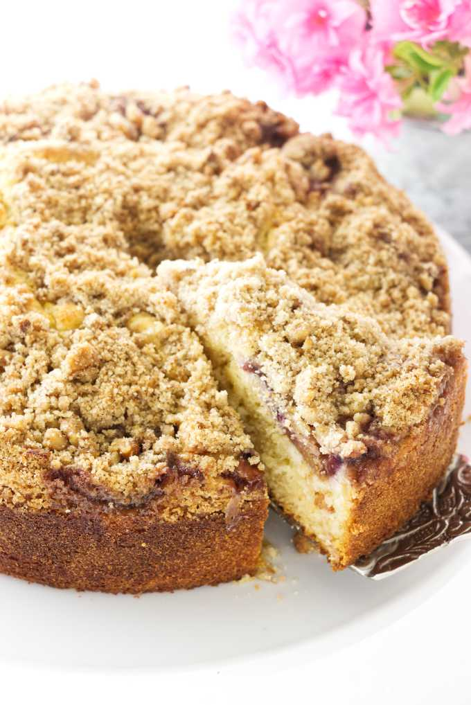 A slice of fresh fig cake with crumb topping being removed from the cake, flowers in the background