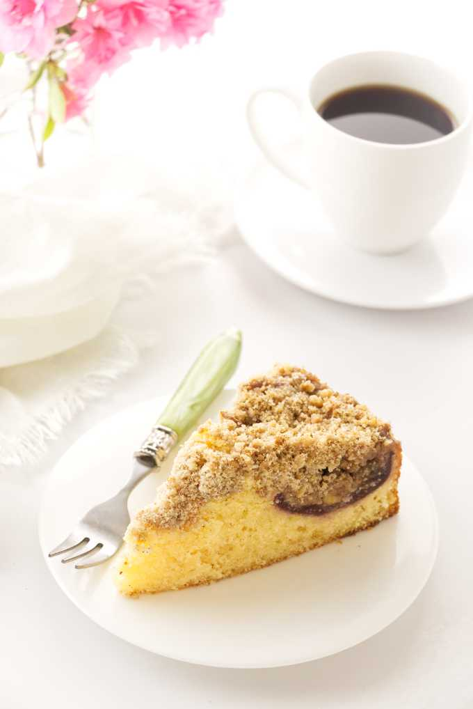 a slice of fresh fig cake on a plate, coffee, napkin and flowers in backgrond