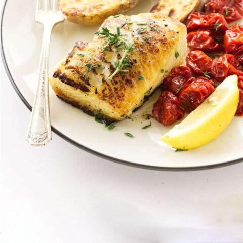 A Chilean sea bass fillet on a dinner plate with tomatoes and lemons.