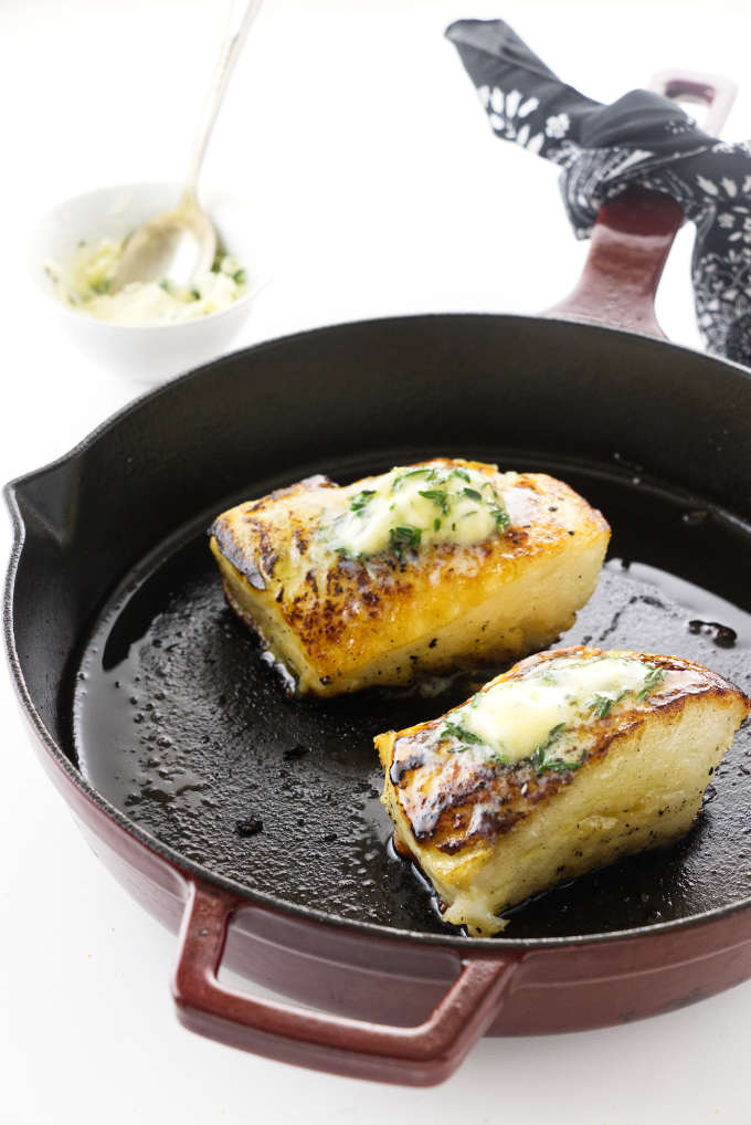 Thyme and butter basted Chilean Sea Bass filets in a skillet