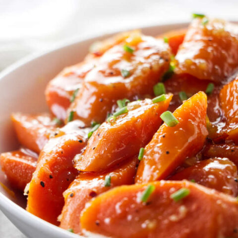 A serving dish with glazed carrots garnished with chives.