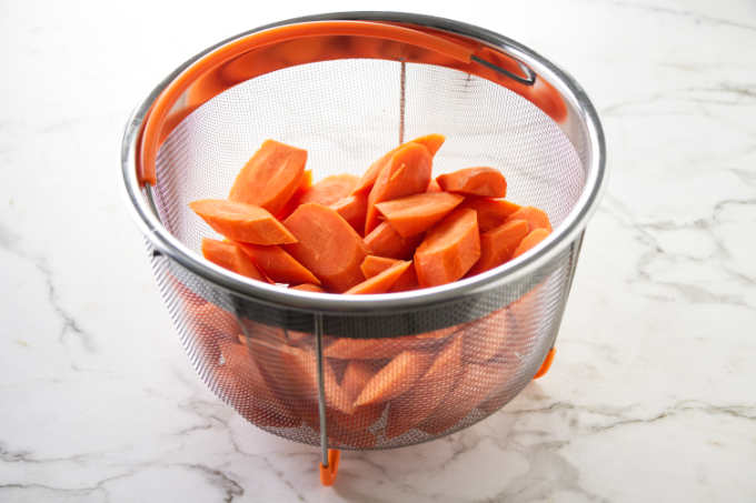 Carrot slices in a steamer basket that fits the Instant Pot.