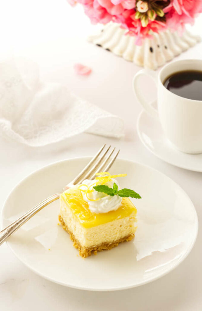 serving of cake on a plate with a fork, coffee, napkin and flowers in background
