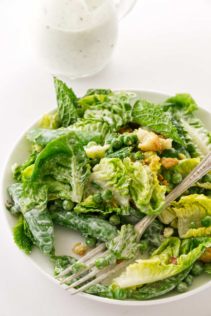A serving of salad with fork, buttermilk ranch dressing in background