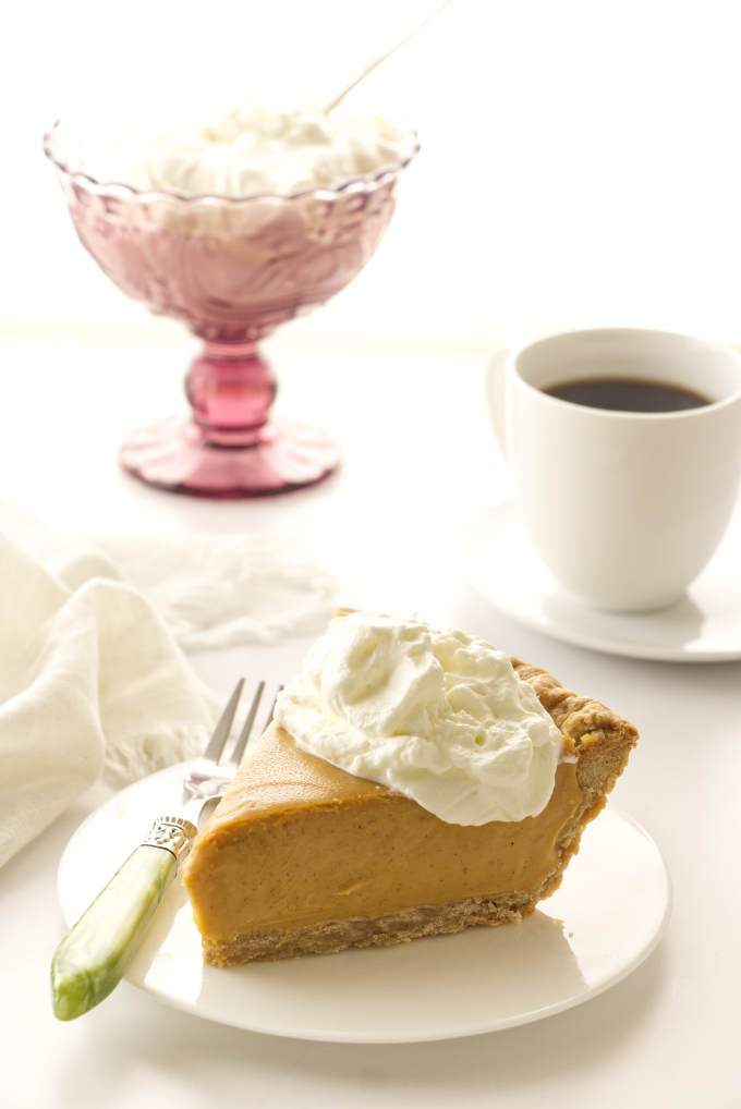 a slice of butterscotch cinnamon pie, cup of coffee and a dish of whip cream