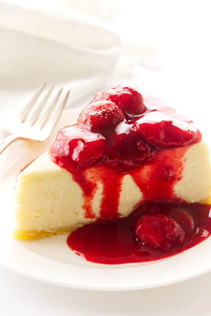 A serving of cheesecake with strawberry topping