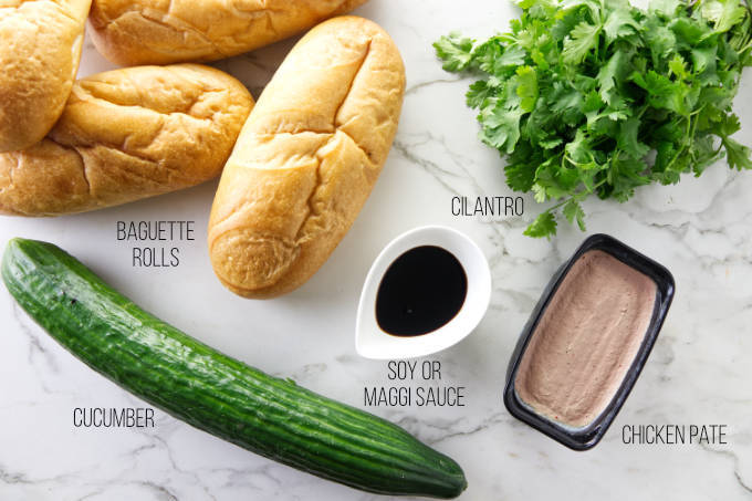 Baguette rolls and fixings for assembling a chicken banh mi sandwich.