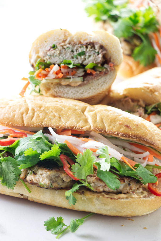 Two chicken banh mi sandwiches stacked on top of each other.