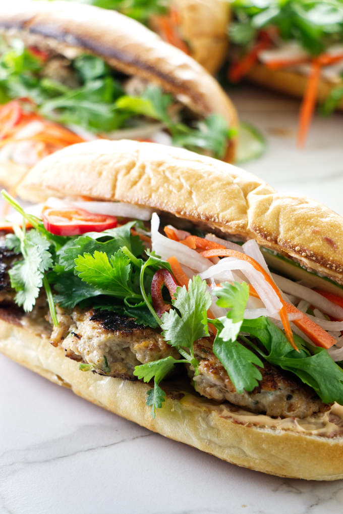 A chicken meatball banh mi sandwich on a French baguette roll.