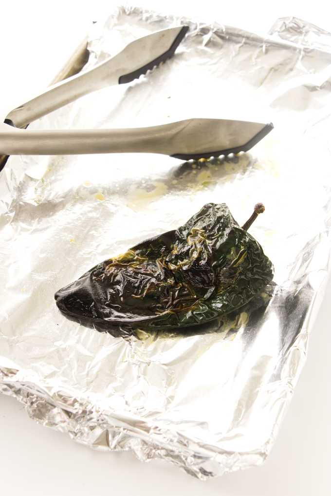 roasted pabloma chili on a foil tray with tongs