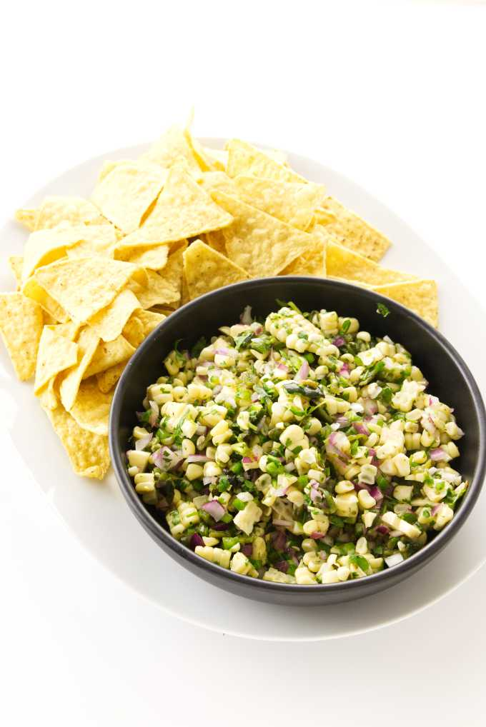 Bowl of chipotle corn salsa on a platter with corn tortilla chips