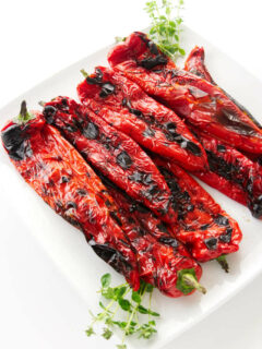A serving plate filled with grilled Italian sweet peppers.