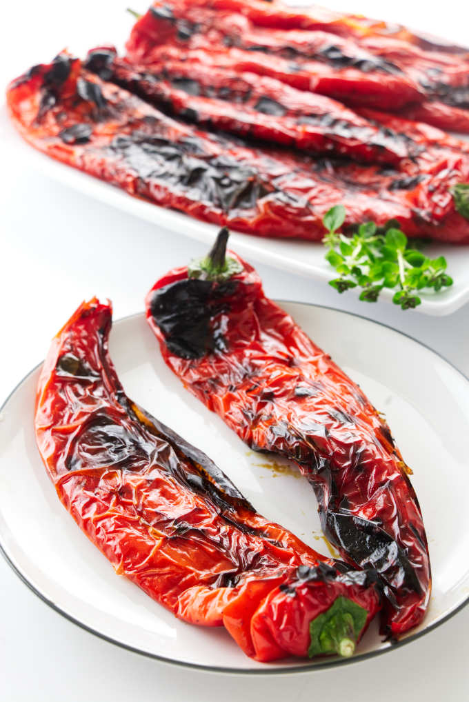 Two grilled sweet peppers on a plate with a serving platter in the background.