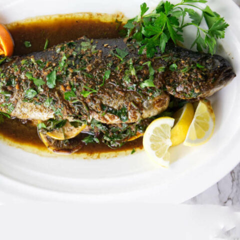A whole baked rainbow trout with citrus pan sauce.