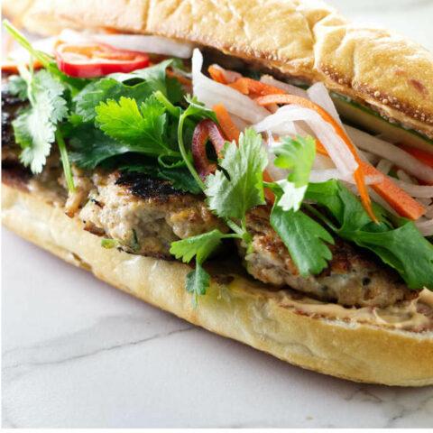 A chicken banh mi sandwich with chicken meatballs.