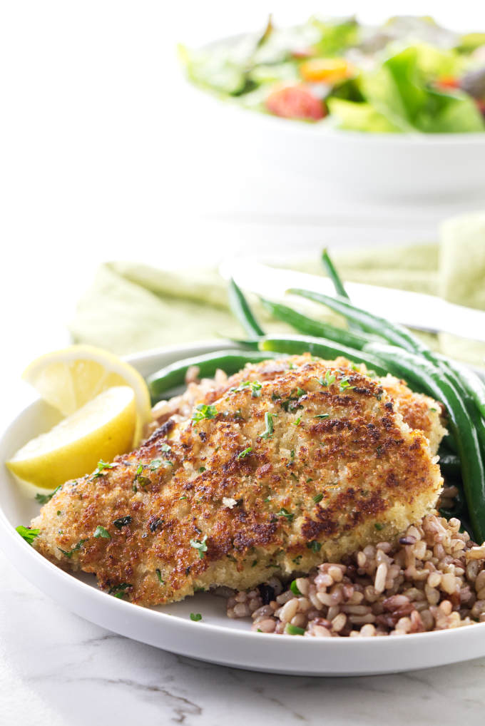 Crispy rockfish fillets on a dinner plate with wild rice blend and green beans.