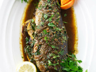 A whole baked rainbow trout on a serving platter.