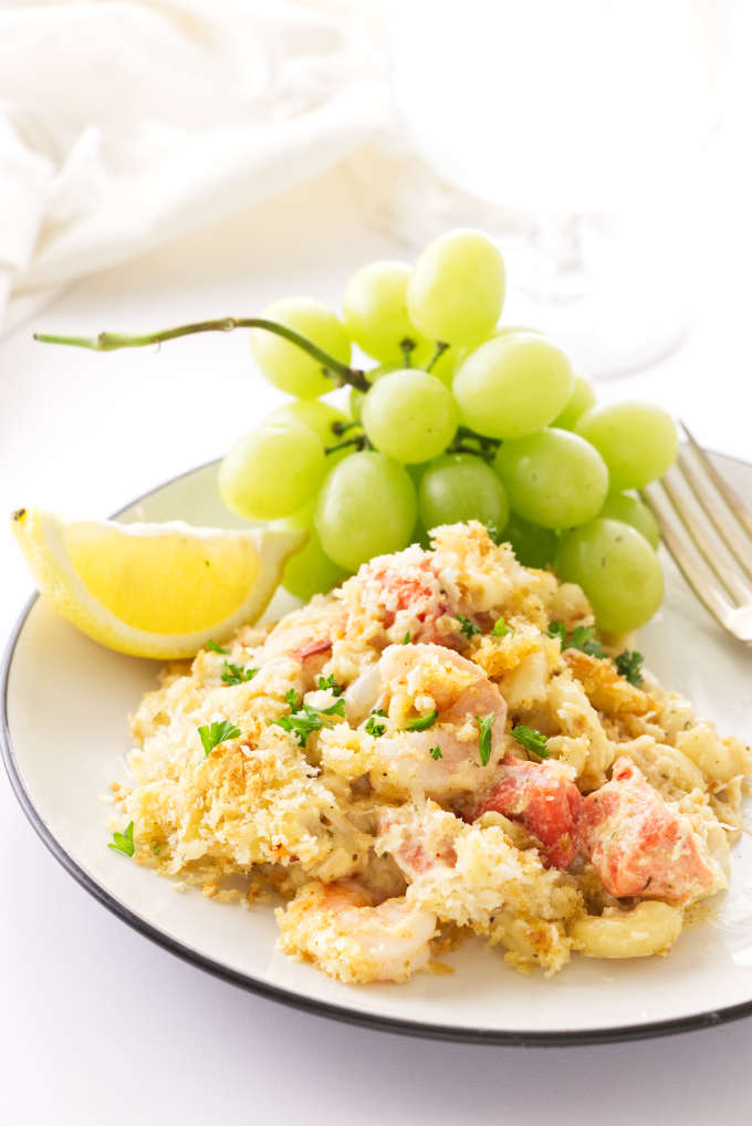 A plate with a serving of seafood mac and cheese and some grapes.