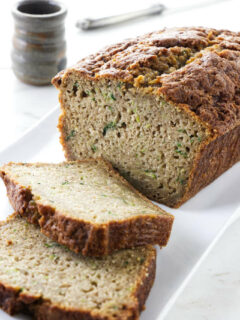 A loaf of zucchini bread with two slices taken off the end.