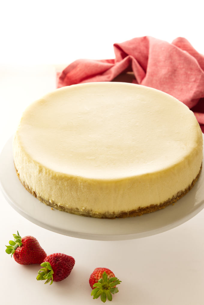 A cheesecake on a cake pedestal.