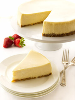A slice of cheesecake on a plate with the larger cheesecake in the background.