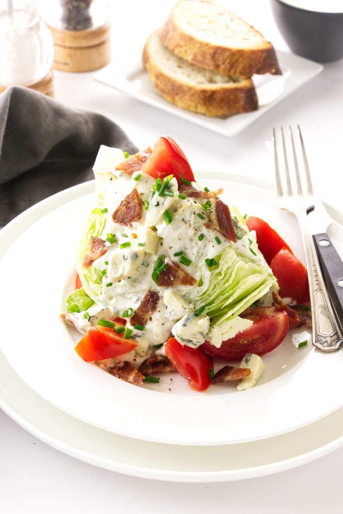 Iceberg lettuce, blue cheese salad dressing on a plate. Napkin, salt/pepper, bread slices in background