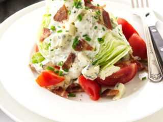 Serving of classic wedge salad on a plate with blue cheese dressing