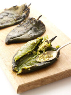 Scooping seeds out of roasted poblano peppers.