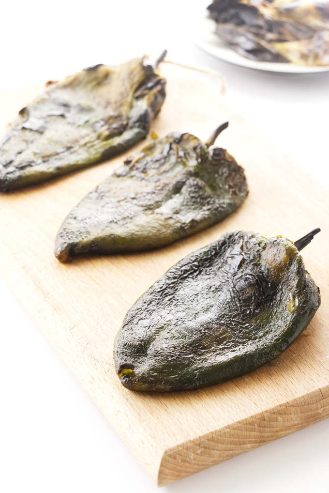 Roasted poblano peppers on a cutting board.