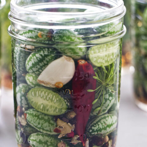Cucamelons and spices in a jar with pickling brine.