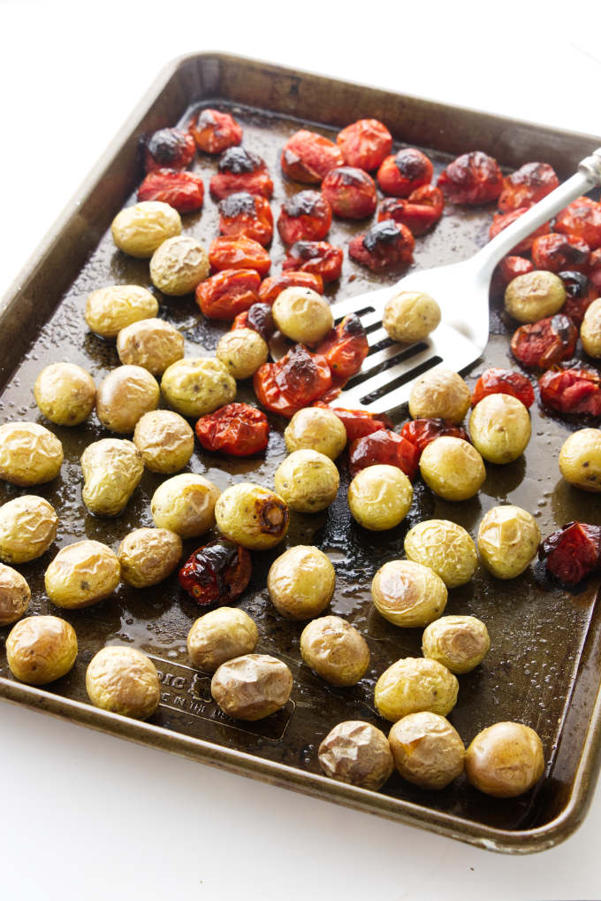 Roasted potatoes and tomatoes on a baking sheet.