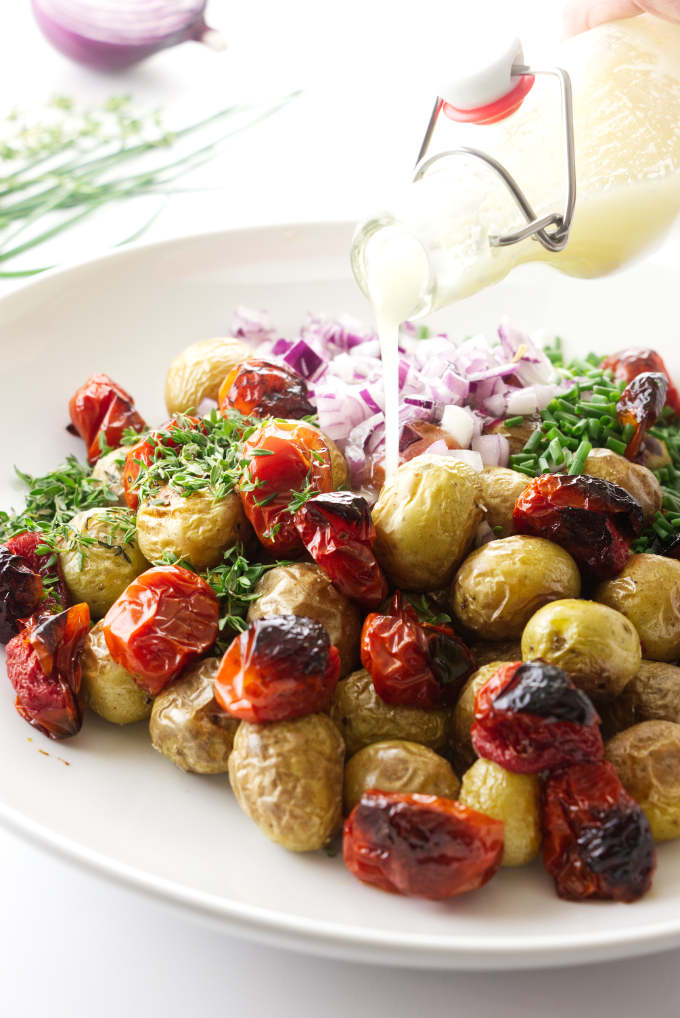 Salad dressing being poured over a roasted potato salad.