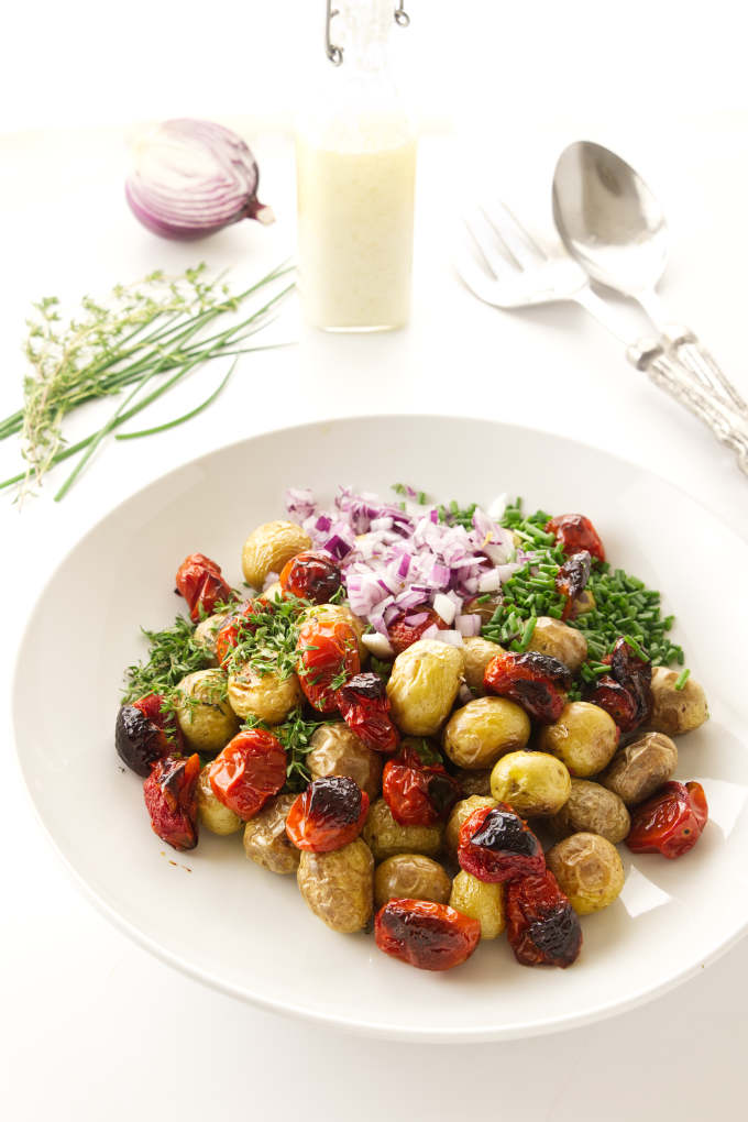 Roasted potatoes and salad ingredients getting tossed in a bowl.