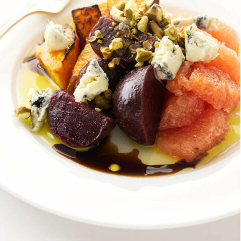 Close up view of a roasted squash and beet salad with grapefruit, blue cheese and pistachios