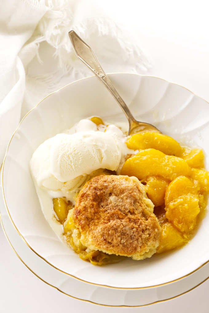 Serving of skillet peach cobbler with ice cream
