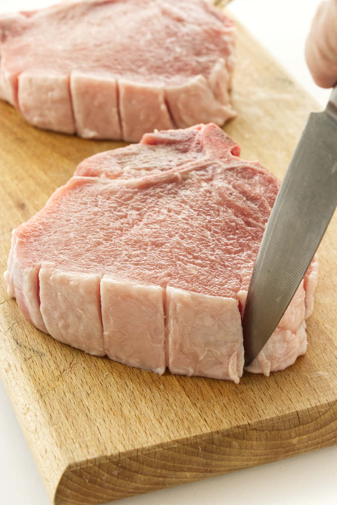 Showing how to slice the fat layer on the edge of pork chops.