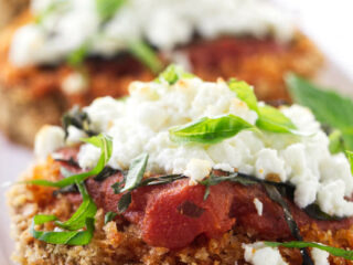 Baked eggplant steaks topped with marinara sauce and goat cheese.