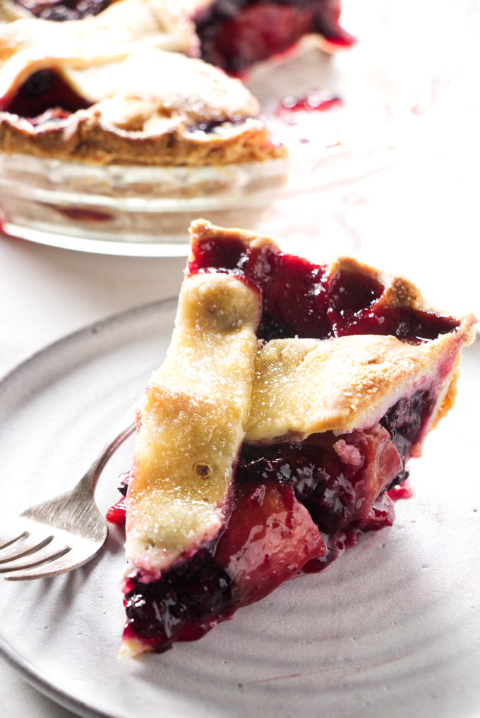 A slice of blackberry peach pie on a plate with a pie dish in the background.
