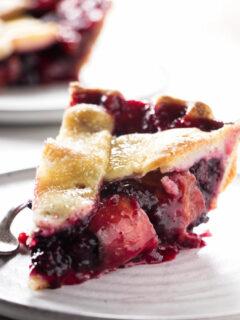 A slice of blackberry peach pie on a plate.