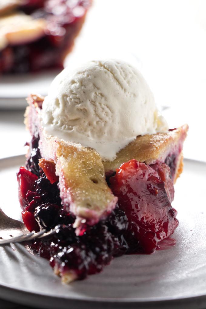 A slice of blackberry peach pie with vanilla ice cream on top.