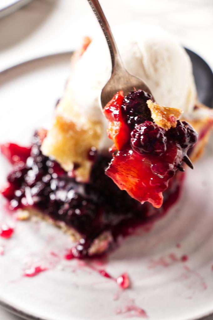 A fork holding a bite of a blackberry peach pie.
