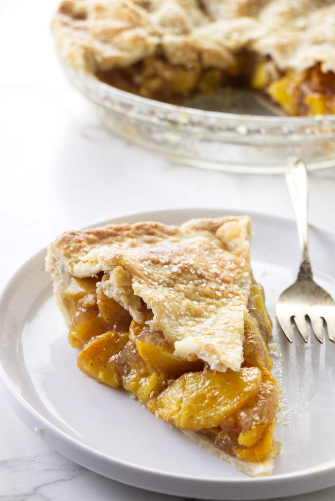 A slice of brown butter bourbon peach pie with a pie dish in the background.