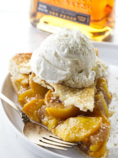A slice of bourbon peach pie with a bourbon bottle in the background.