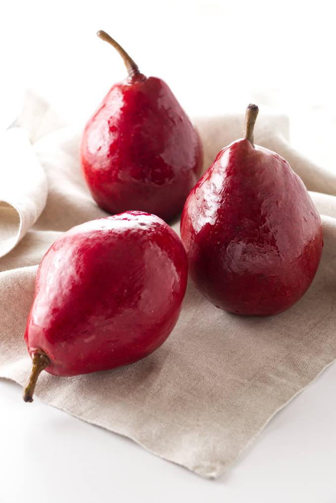 Three red pears on a napkin