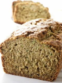 A loaf of gluten free zucchini bread sliced open to see the tender texture.