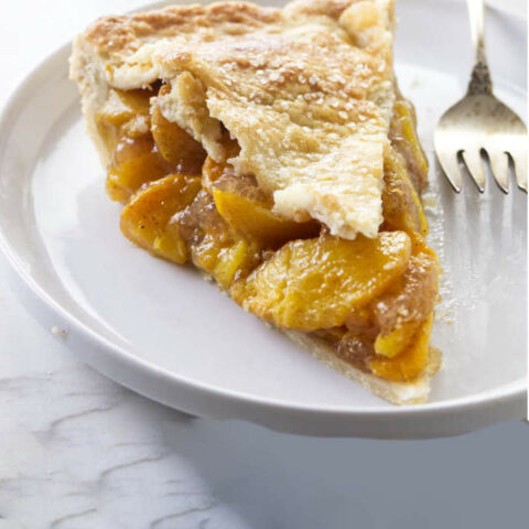A slice of peach pie with brown butter and bourbon.