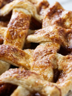 Close up of a lattice pie crust baked with sparkle sugar on top.